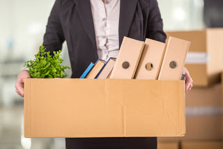 Person carrying box of work possessions