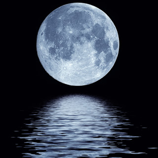 Full moon rising over the water