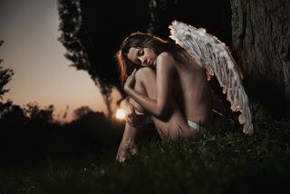 Angel hugging own knees looking despondent