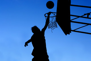 Man in silhouette shooting for basketball goal