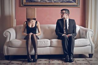 Man and woman sitting apart on sofa, woman wearing box on head