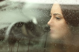 Woman looking sad through car window