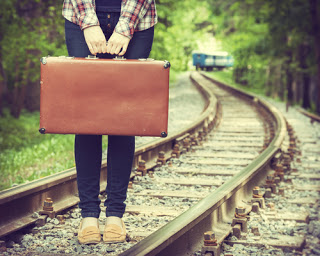 Girl on railway tracks with suitcase