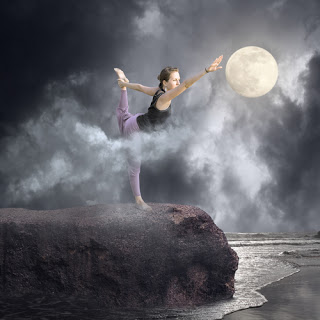 Woman doing yoga on rocks at beach, reaching for moon