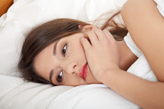 Woman lying on her side, looking bored