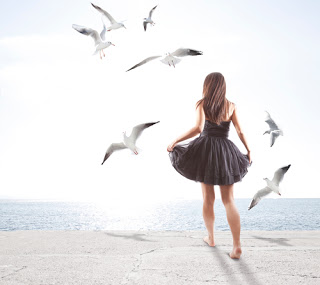 Woman walking away surrounded by birds