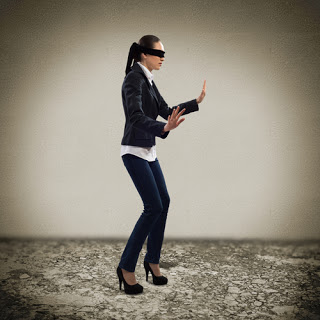 Blindfolded businesswoman stumbling along an empty room