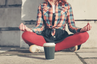 Woman meditating in a busy street