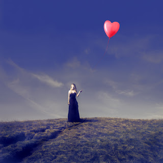 Woman in field holding heart-shaped balloon