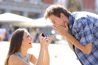 Woman on bended knee proposing to shocked man