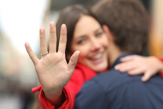 Smiling woman hugging man, holding out hand with engagement ring on it
