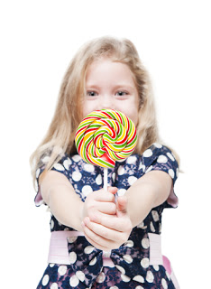 Little girl holding large lollipop and smiling