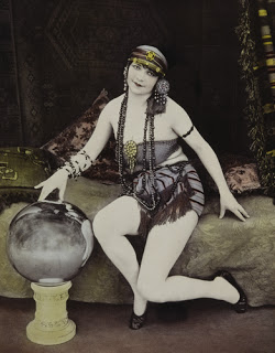 Black and white photo of 1920s woman looking over a crystal ball