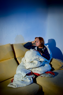 Woman on couch with blanket, holding head