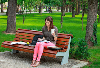 Girl writing in diary on park bench