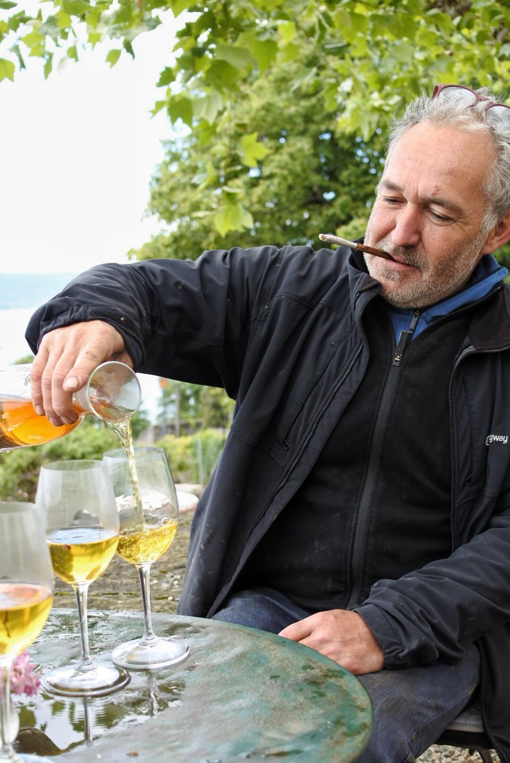 Gilles, happily pouring some vine tea while puffing on dried vine leaves