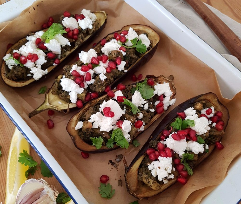 sumac and coriander stuffed aubergines topped with pomegranate seeds and feta