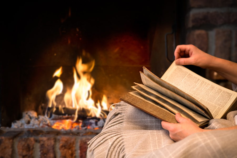 hands of woman reading book by fireplace