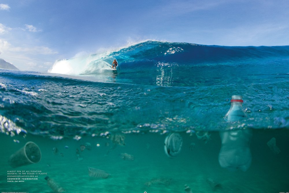 Platic bottle floating in the beautiful ocean with a wave coming on