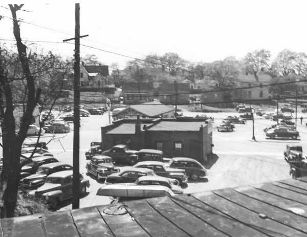 The area sandwiched between East Black Street and the rear of the commercial row of buildings on Main Street was used for parking and storage warehousing for businesses. This image was taken in ca. 1940s.