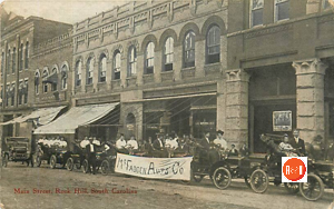 Postcard view of McFadden Auto Co., showing off their cars along Main Street, ca. 1910