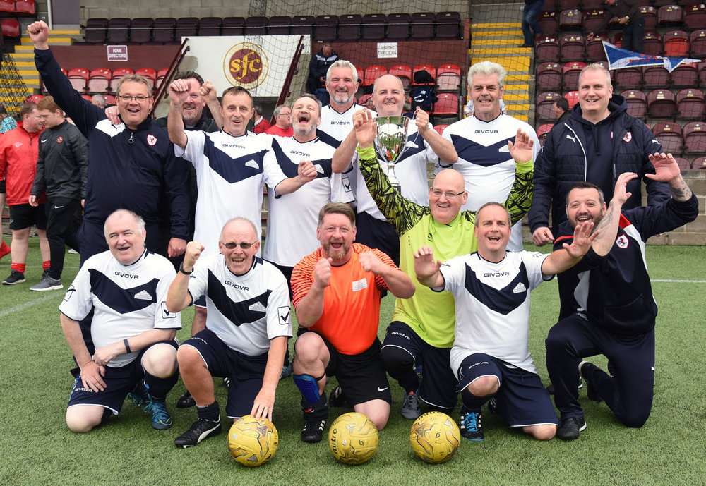 Raith Rovers team and coaches celebrate after receiving the Trophy from Walking Football Scotland Chairman Gary McLaughlin