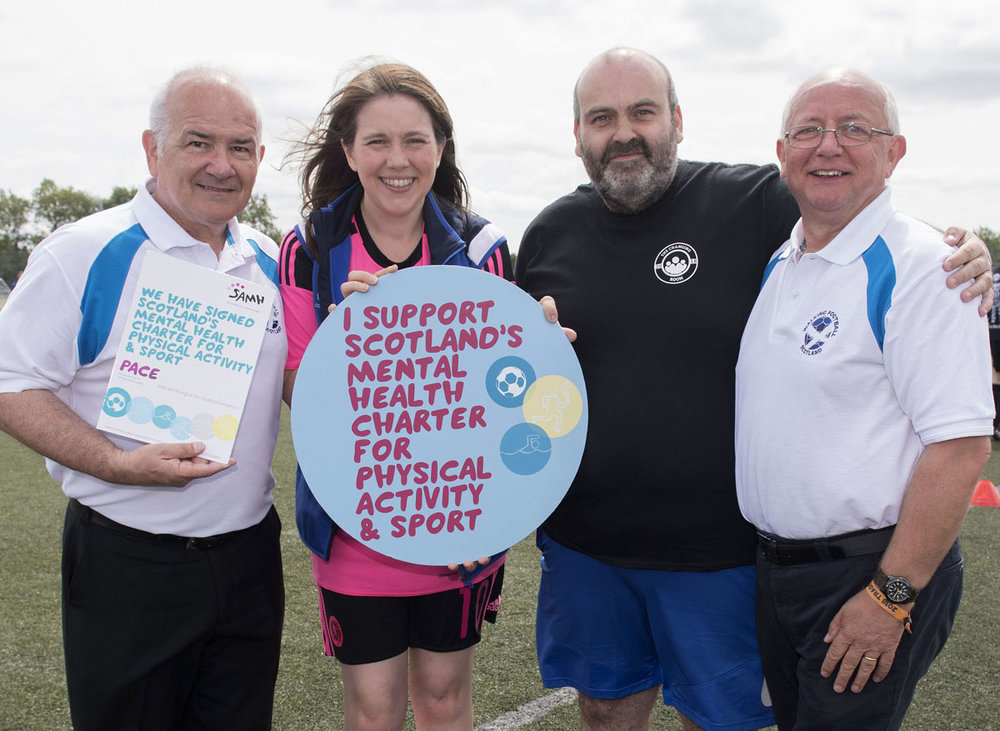 The photograph shows l-r chair Gary McLaughlin, Aileen Campbell MSP, Robert Nesbitt of SAMH and Treasurer David Hyland with the Charter Documentation in June this year.