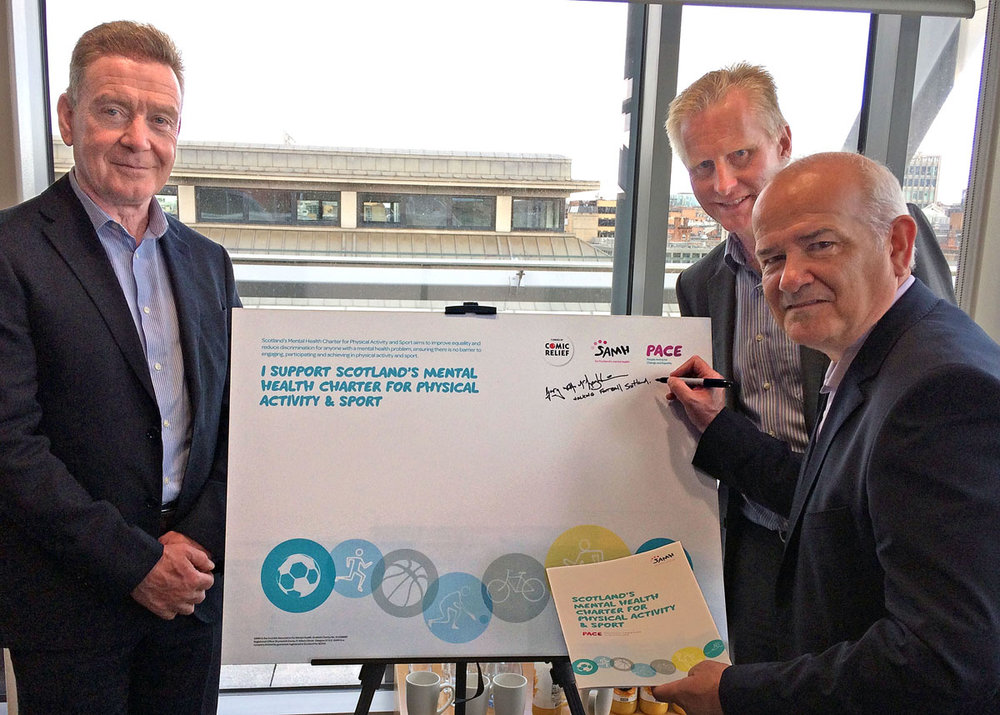 l-r Graeme Henderson Director of Delivery and Development SAMH, Ian Beattie vice Chair of SAMH look on as Walking Football Scotland Chair Gary McLaughlin signs up to the Mental Health Charter.
