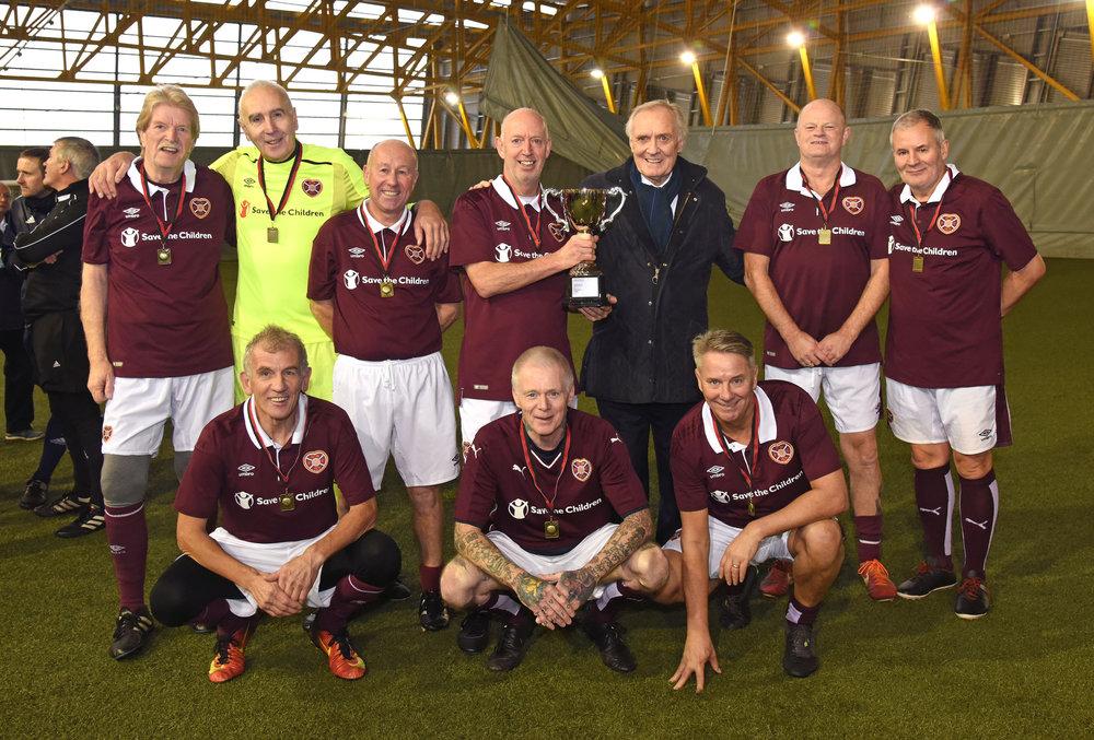 Hearts 56 receive last seasons National League Trophy from Scottish football legend David Hay.