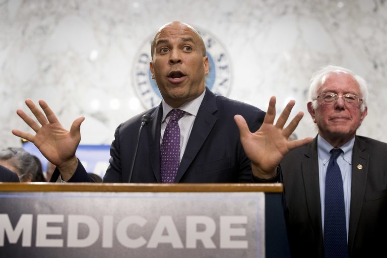 Sen. Cory Booker, D-N.J., left, accompanied by Sen. Bernie Sanders, I-Vt., right, speaks during a news conference on Capitol Hill in Washington, Wednesday, Sept. 13, 2017, to unveil their Medicare for All legislation to reform health care. (AP Photo/Andrew Harnik)