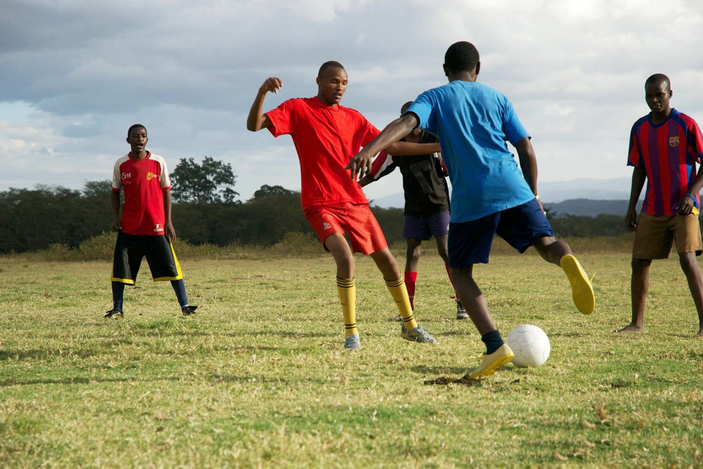 Two Feet Kids Playing Soccer Blue Sky.jpg