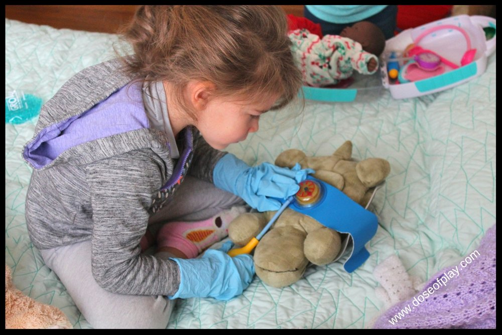 Time for a check up! Four year old engaged in medical play on a night light stuffed animal.