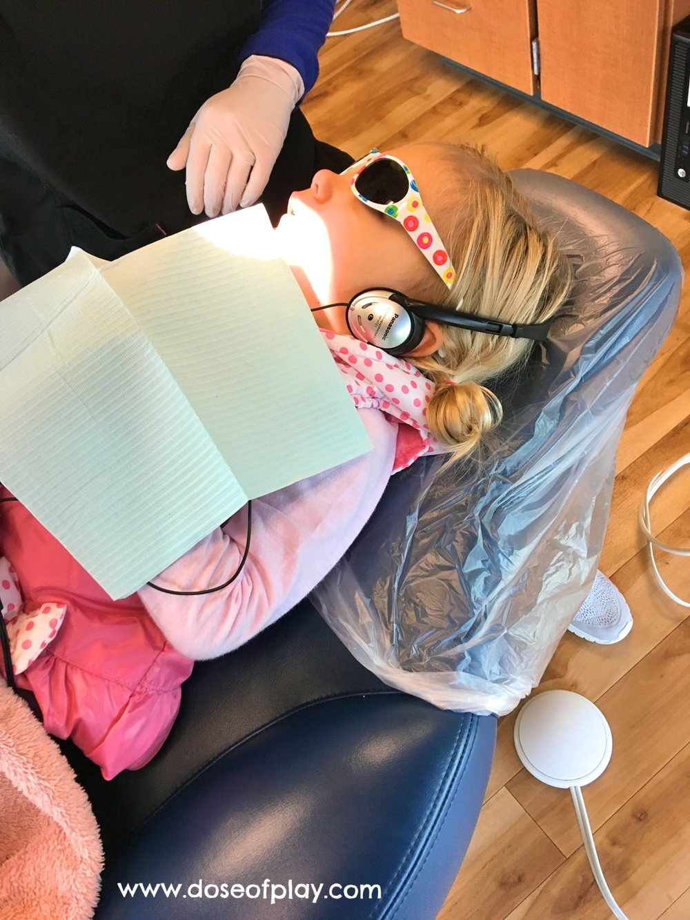 Two year old Quinn coped very well with her thorough exam and cleaning with the help of sunglasses and headphones to enjoy a movie on the ceiling! This was her first successful medical experience without a comfort hold - don't worry if your child prefers to use a comfort hold at this age.