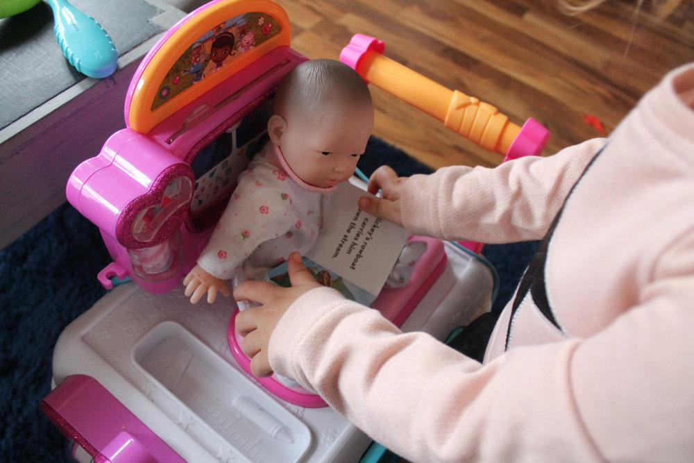This is a flashback to last year when my 3-year-old daughter positioned her baby doll sitting up (YES my love, YES), gave her a book as a distraction and proceeded to give her a checkup. These are powerful coping strategies for kids and important small ways parents can advocate for care to be provided during their child's medical experiences. Check out my previous post dispelling 5 Myths about IV starts that specifically shares evidence-based research about how  kids cope better with needle procedures when sitting up .
