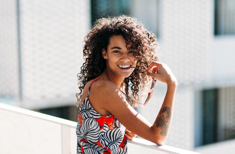 Stocksy_Kayla-Snell-Woman-standing-on-balcony.jpg