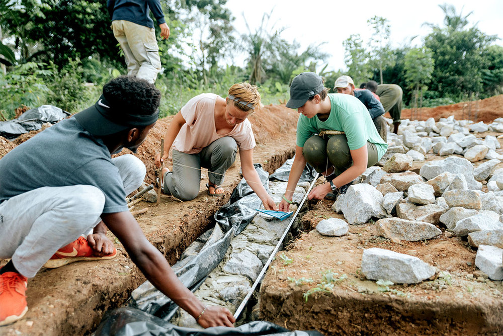 Team leader Samantha McPadden (center), with volunteers Ashley Bonawitz (UNC Charlotte alum) and Fritz Ababio, setting column lines at the foundation. Photo by Tiffany Ortega