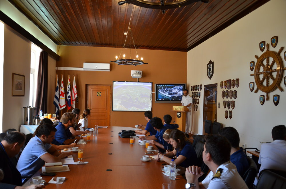 Students receive a welcome briefing on Souda Naval Base from Captain Stylianos Papadakis, director of the Command Directorate at Souda Naval Base (not pictured).