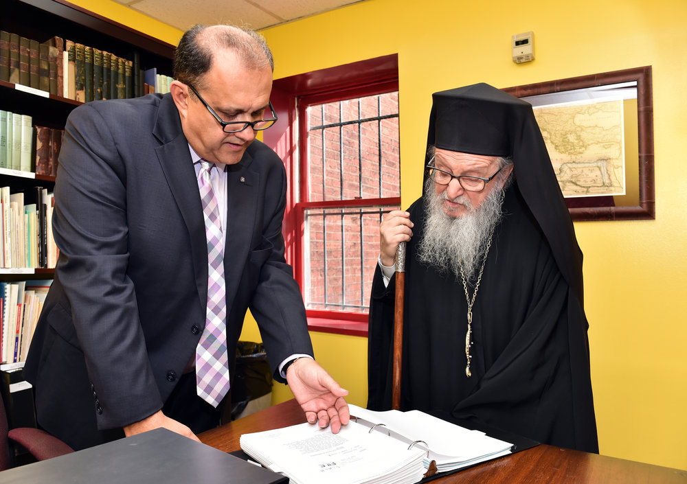 Nick Larigakis shows His Eminence Archbishop Demetrios of America an example of the thirty one volume set of declassified documents on the Cyprus invasion of 1974, compiled by Gregory Graves.