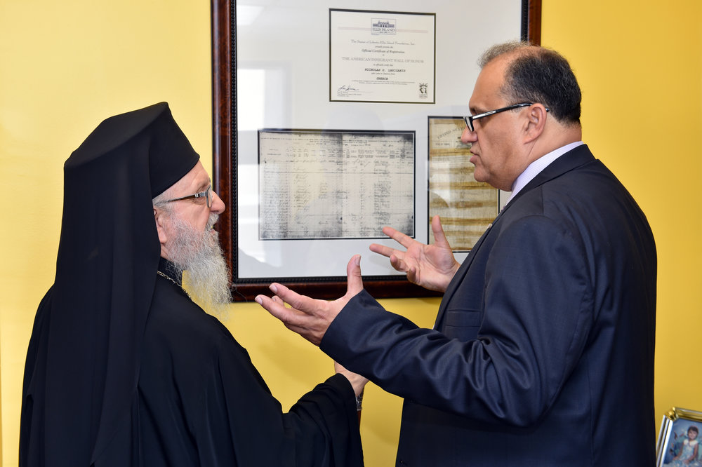 Nick Larigakis shows His Eminence Archbishop Demetrios of America archival documents of the journey of his family from Greece to America.