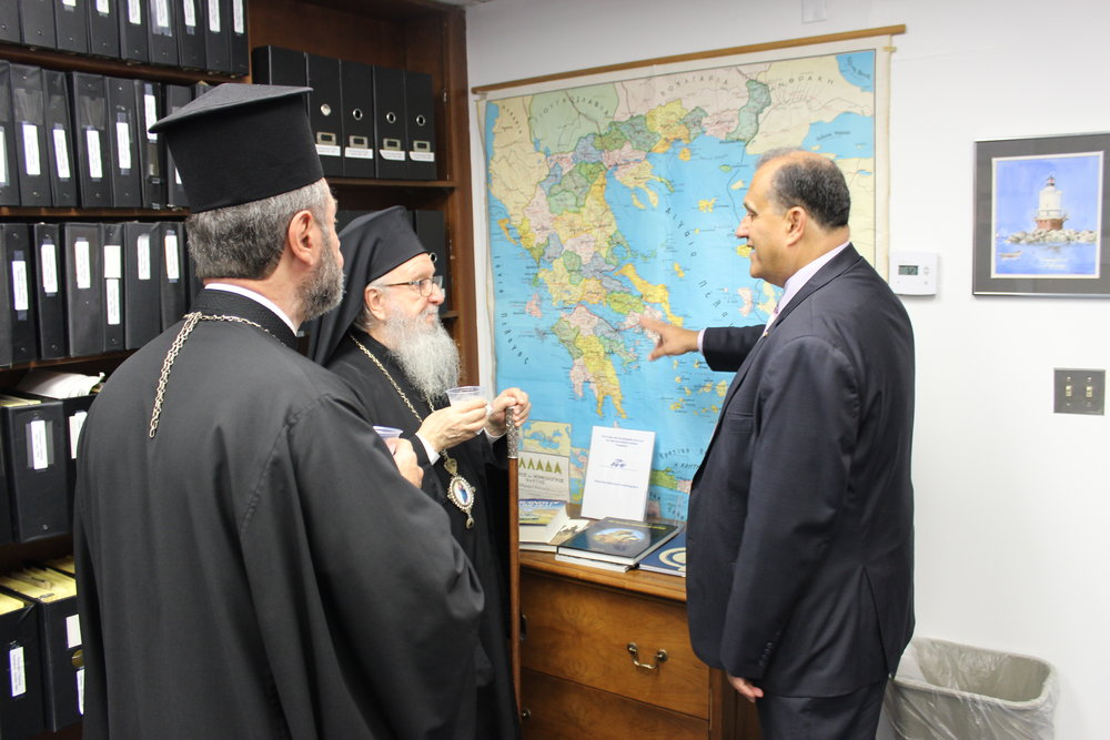 His Eminence Archbishop Demetrios of America, AHI President Nick Larigakis, and Bishop Sevastianos of Zela discussing the heritage of their families in front of a map of Greece.