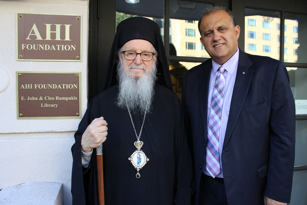 His Eminence Archbishop Demetrios of America and AHI President Nick Larigakis in front of the sign identifying the AHI Foundation E. John & Cleo Rumpakis Library situated at the front entrance to the Hellenic House.