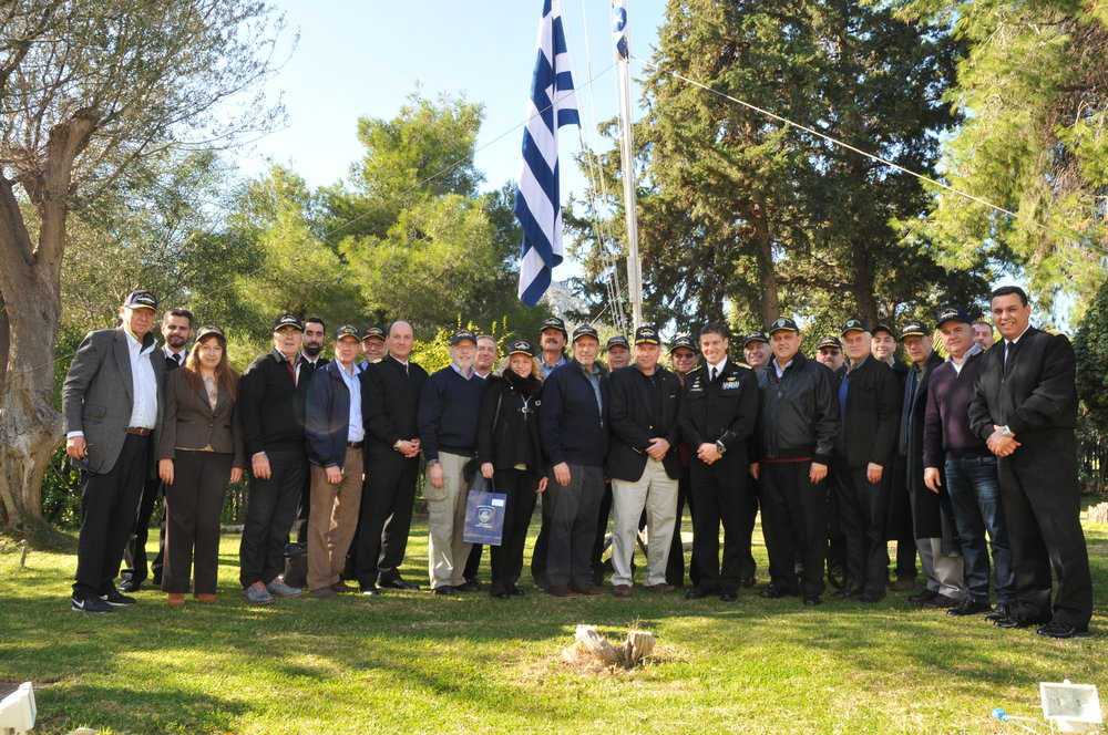 Delegation poses with naval caps provided by Vice Admiral Pavlopoulos outside his residence at Salamis Naval Base.