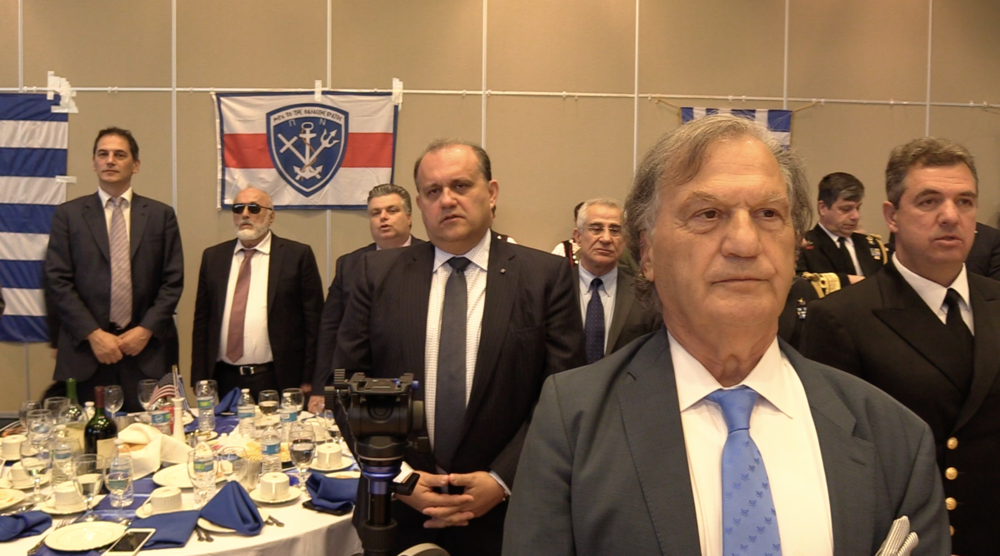 Minister Panagiotis Kouroumplis, Minister of Maritime Affairs & Insular Policy (with glasses) joins guests during the Greek National Anthem.