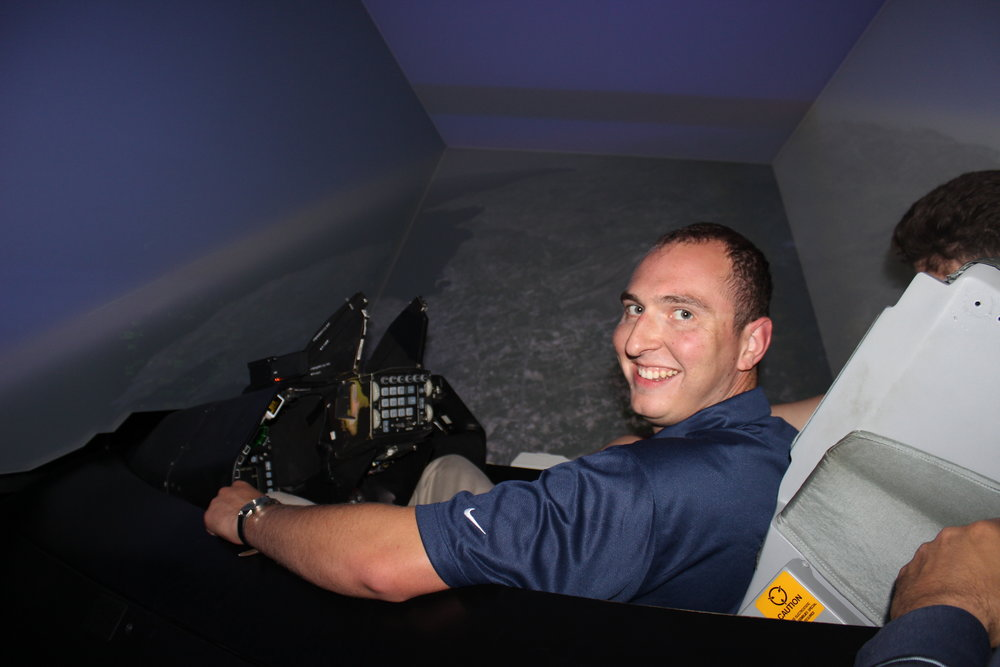 Student participant Michael Zoumadakis inside an F-16 flight simulator at the 115th Combat Wing.