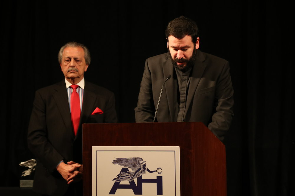 Rev. Presbyter Peter Kostakis, Holy Trinity Greek Orthodox Church of Dallas, provides the Invocation with Master of Ceremonies George Naftis to his right.