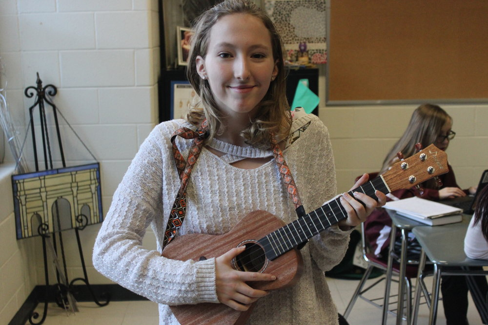 Emma Williamson strums her ukulele with a smile.