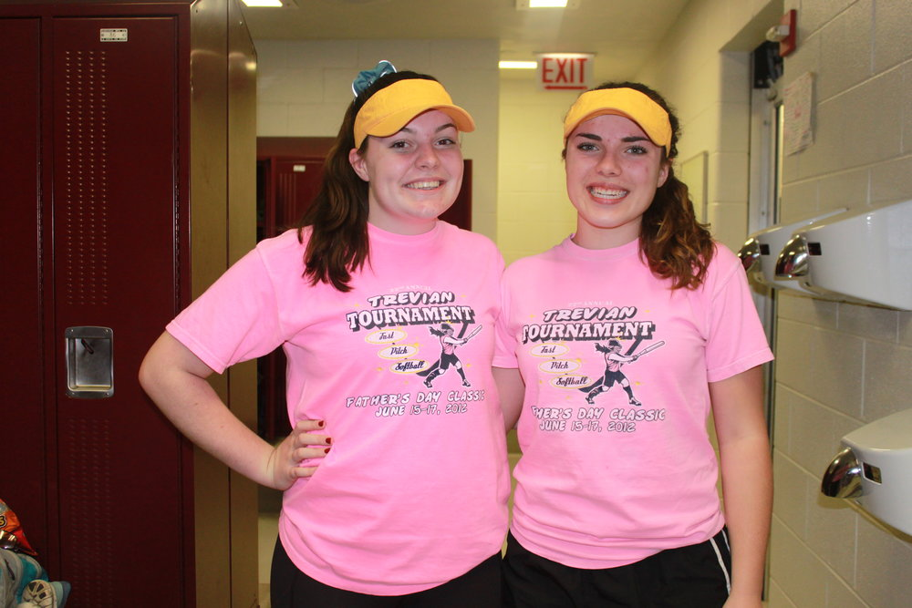 Caroline Merck and Maddy Schoeff match in yellow visors and pink shirts.