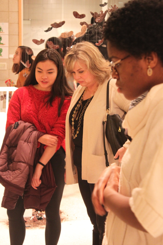 Lauren Fujishima and Jennifer Ogumike looking at Logan Abrub's 20 hour project.