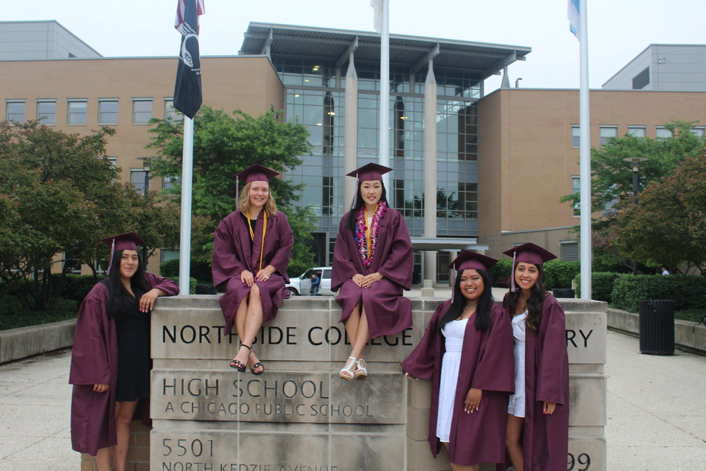 Smiling fondly, a group of senior girls stand in front of Northside before graduation