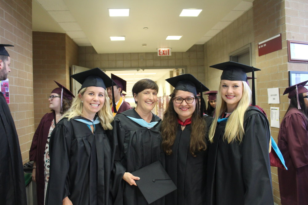 Keen to see the impact Northside's graduating class of 2018 has on the world, four teachers stand smiling amid throngs of seniors